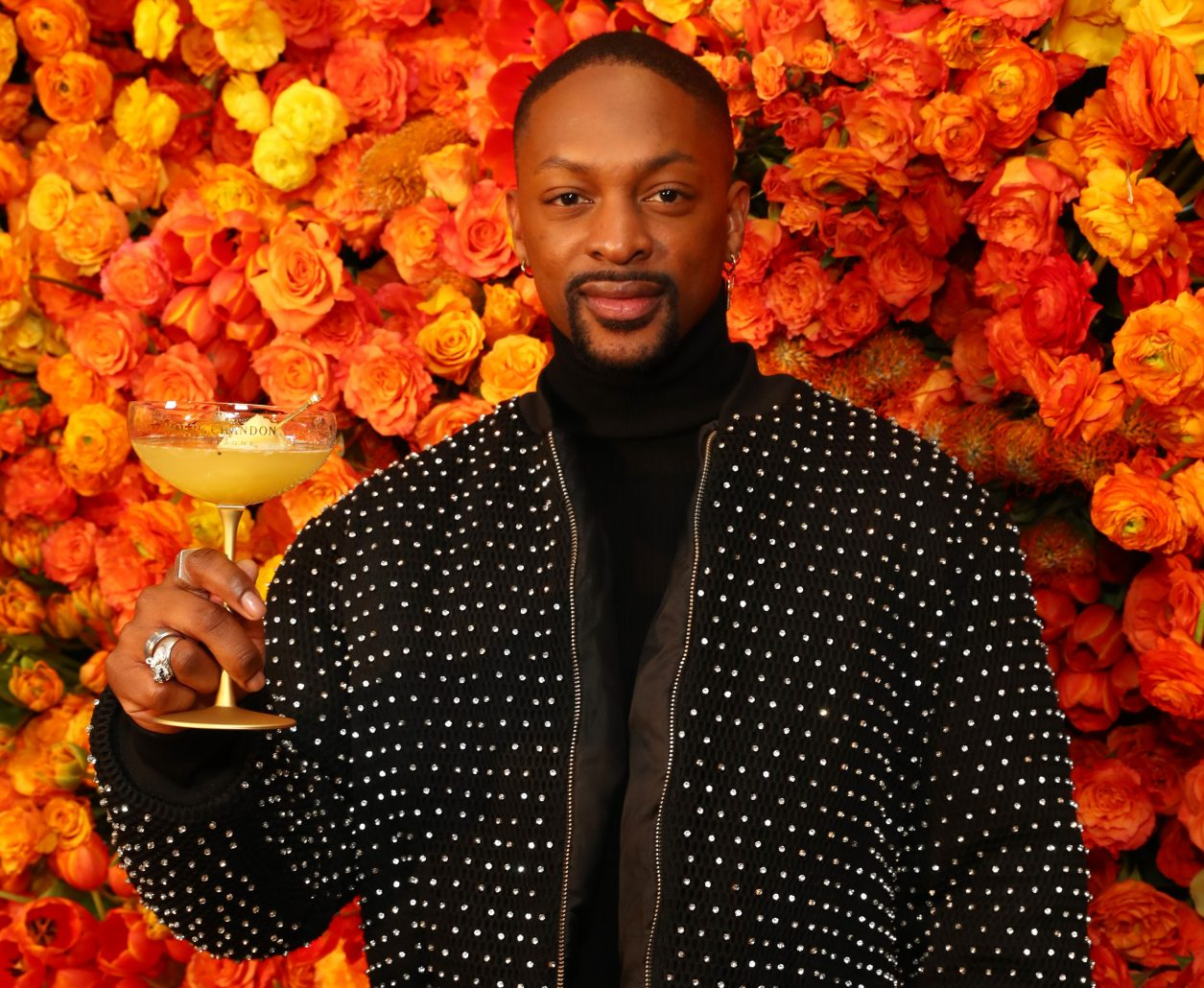 """BEVERLY HILLS, CALIFORNIA - DECEMBER 16: Laquan Smith poses with the signature cocktail """"The Moet Golden Hour"""" at the 77th Annual Golden Globe Awards Show Menu Unveiling at The Beverly Hilton Hotel on December 16, 2019 in Beverly Hills, California. (Photo by Joe Scarnici/Getty Images for Moët & Chandon)"""